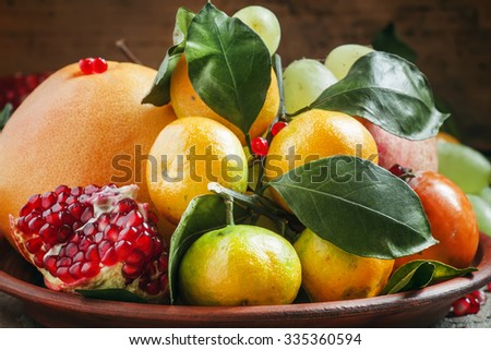 Clay dish with winter fruits: grapefruit, tangerines, persimmons, pomegranates with leaves on the old wooden table, still life, selective focus - stock photo