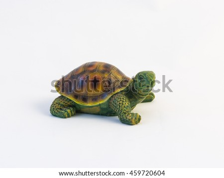 Clay figurines of a crawling turtle on a white background