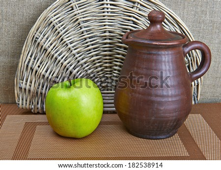 Clay jar and green apple standing on table  - stock photo