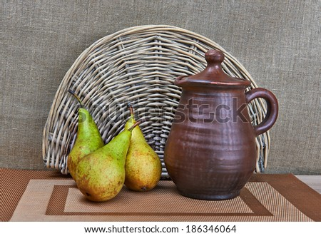 Clay jar and green pears standing on table - stock photo