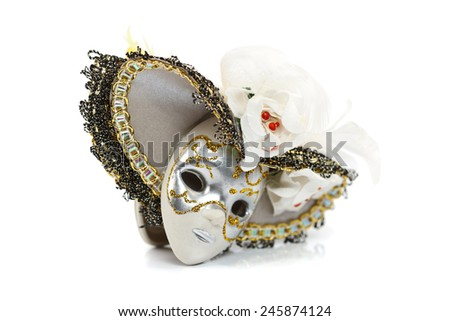 Clay mask with silver and golden decoration and hat over white background - stock photo