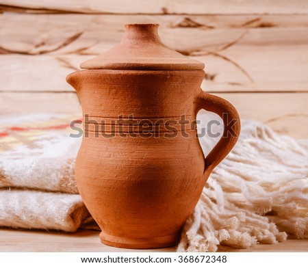 clay milk jug isolated on wooden background.