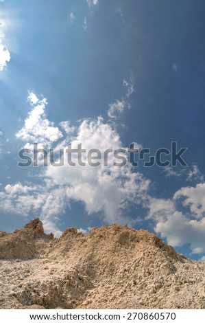 Clay pit in the background of a beautiful blue sky - stock photo