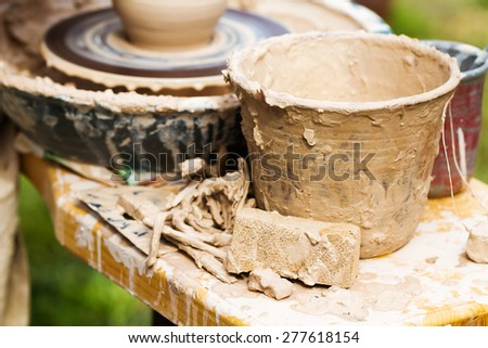 Clay pot on a pottery wheel in outdoor workshop