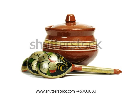 Clay pot with wooden spoons - stock photo