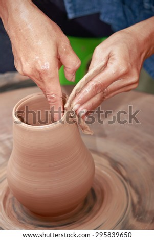 Clay potter artist making pot shape on wheel pedestal - stock photo