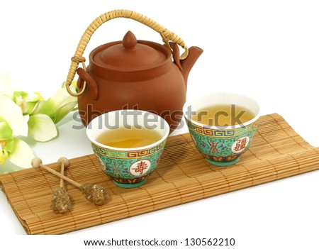 clay teapot and cups of tea isolated on white background - stock photo
