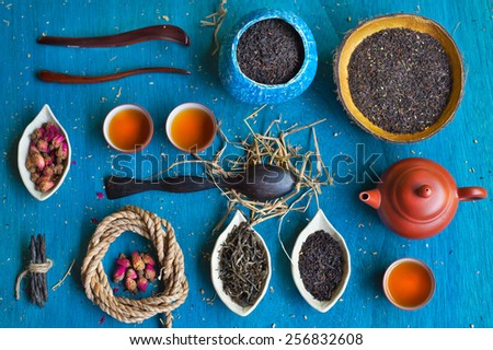 Clay teapot, three teacups, coil of rope, rosebuds, three wooden spoons, two handmade coconut bowls and three saucers in the form of petals with different sorts of tea on blue wooden background. - stock photo
