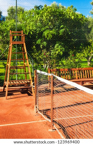 Clay tennis court in a resort garden setting with wooden bench and umpire chair - stock photo