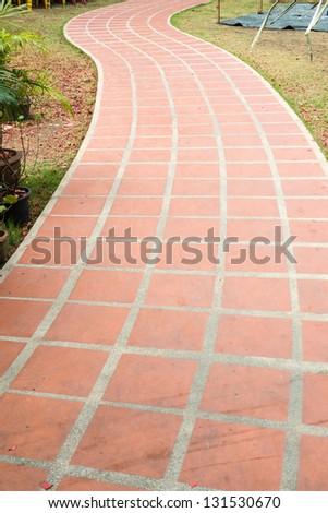 clay tile walk path on green grass - stock photo