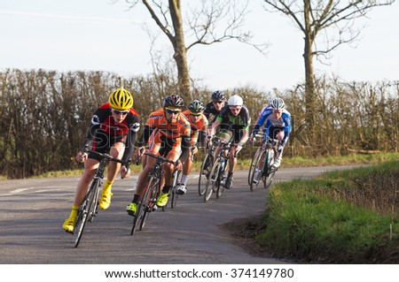 CLAYDON, UK - MARCH 8: Riders competing in the Roy Thame Cup road racing cycling event exit Claydon village en route to Gawcott on March 8, 2014 in Claydon.