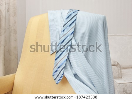 clean  and tie shirt hanging on a chair