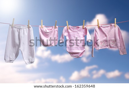 Clean baby girl clothes on the outdoor clothesline  - stock photo