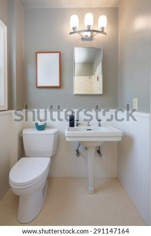 Clean bathroom and toilet with mirror and white wood. - stock photo