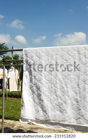 Clean bedding hanging to dry. Housework, laundry in sunny day. - stock photo
