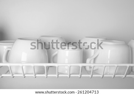 Clean cups drying on metal dish rack close up