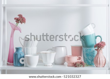 Clean dishes and flowers on wooden shelf