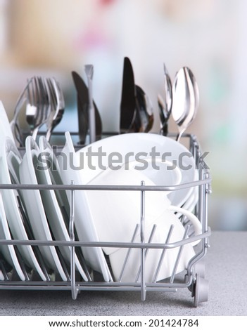 Clean dishes drying on metal dish rack on light background