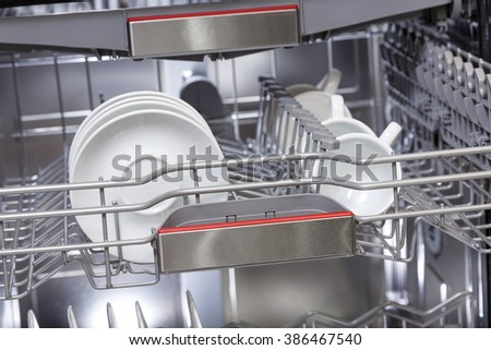 Clean dishes in open dishwasher machine