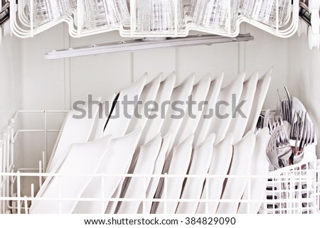 Clean dishes inside of a dish washing machine. - stock photo