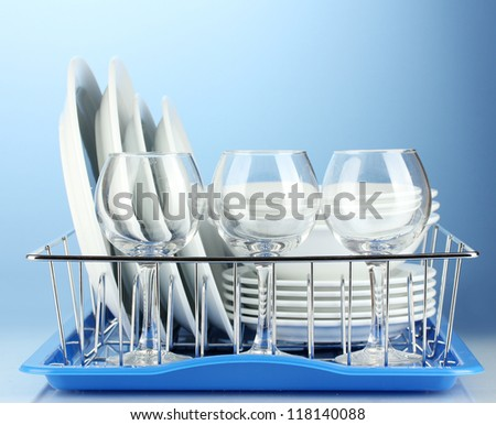 clean dishes on stand on blue background - stock photo