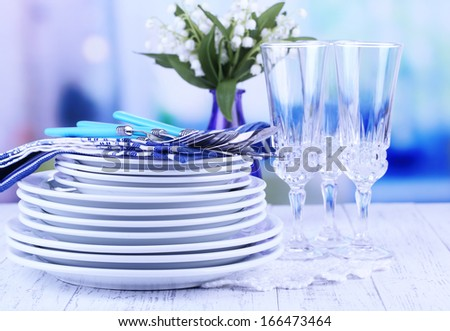 Clean dishes on wooden table on light background - stock photo