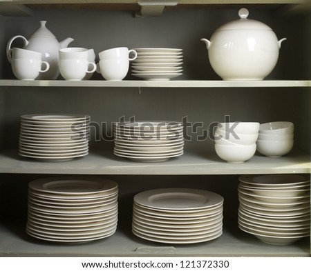Clean Dishes & Other Tableware placed on a wooden shelf - stock photo