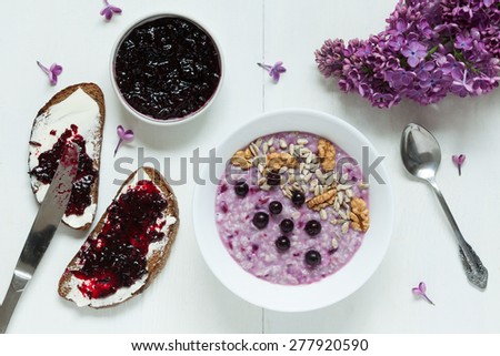 Clean eating diet healthy breakfast. Oatmeal porridge muesli with nuts, sunflower seeds, berries and berry jam. Two toasts with butter and jam. Served on white kitchen table background with lilac - stock photo