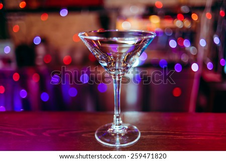 clean empty cocktail glass martini on a dark bar counter with a background of neon lights and bokeh - stock photo