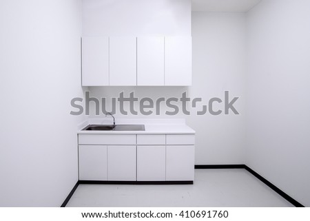 Clean empty white kitchen with sink and cabinet - stock photo
