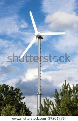 Clean energy white wind turbine in green field with small trees. - stock photo