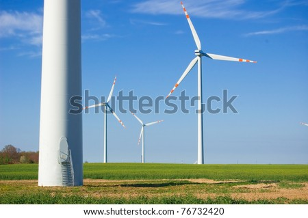 Clean energy. Windmills on green field. - stock photo