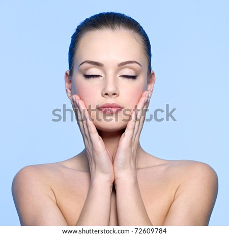Clean face of beautiful teen girl touching her cheeks. Pretty young female with closed eyes - stock photo
