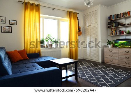 Clean Family Room With Blue Couch, White Brick Wall And Yellow Curtains.  Design Interior