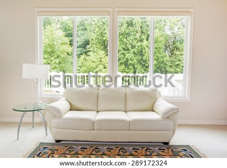 Clean family room with white leather couch and large windows showing bright green trees in background. - stock photo