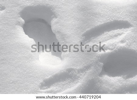 Clean Footprints In Snow Texture Background - Clean white fluffy powder snow with deep footprints, winter ground texture photo. - stock photo