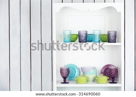 Clean glasses, plates and cutlery on shelves in kitchen cupboard - stock photo