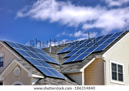 Clean green energy efficient saving source photovoltaic solar panels cells modules on residential house roof over cloudy sky producing free renewable electricity  - stock photo