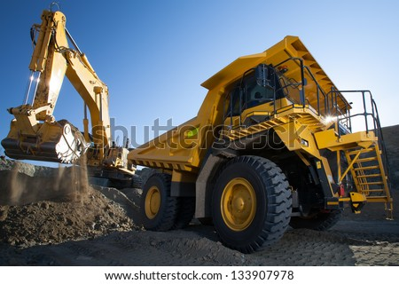 clean image of yellow excavator loading soil on a truck at mine back lit - stock photo