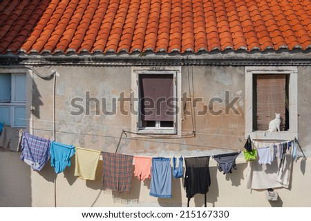 Clean laundry drying on the rope in front of the old house. - stock photo