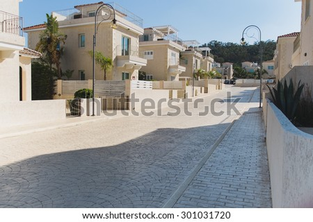Clean light street with pavement trees and the same neat white houses covered with red tile, Protaras in Cyprus - stock photo