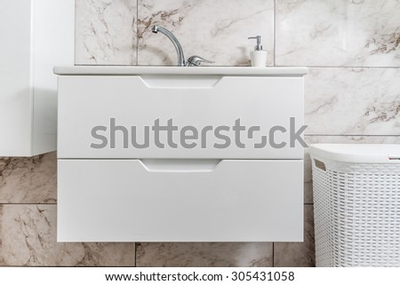 Clean, modern bathroom interior with white sink, faucet and closet - stock photo