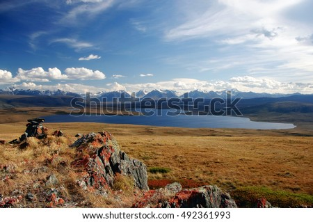 Clean mountain lake on the background of snow covered mountains and glaciers rocks  with red lichen on the foreground under white clouds and blue sky, Plateau Ukok, Altai mountains, Siberia, Russia