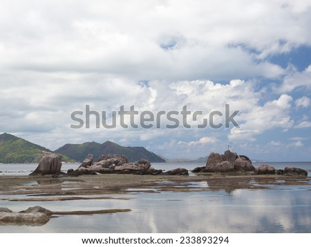clean ocean at low tide and a lot of clouds on the island of Praslin, Seychelles - stock photo