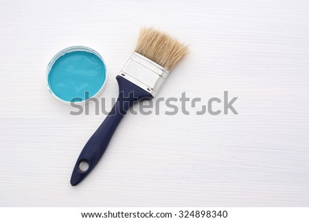 Clean paintbrush and small container of blue paint on a wooden board painted white - stock photo
