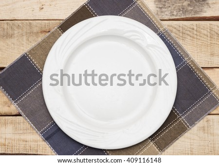 Clean plate with napkin on wooden background.