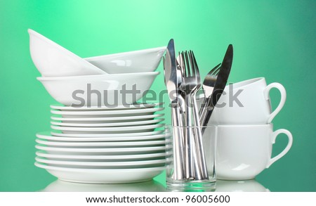Clean plates, cups and cutlery on green background - stock photo