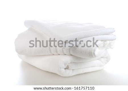 Clean, Pristine White Towels Stacked Isolated on a White Background - stock photo