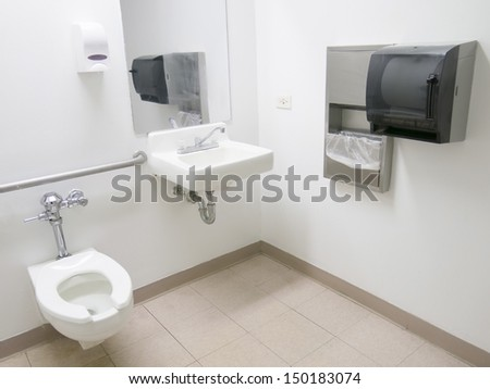 Clean public hospital bathroom with handrail soap and paper towel dispenser - stock photo