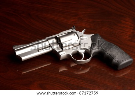 Clean .357 revolver laying on reflective wooden table - stock photo